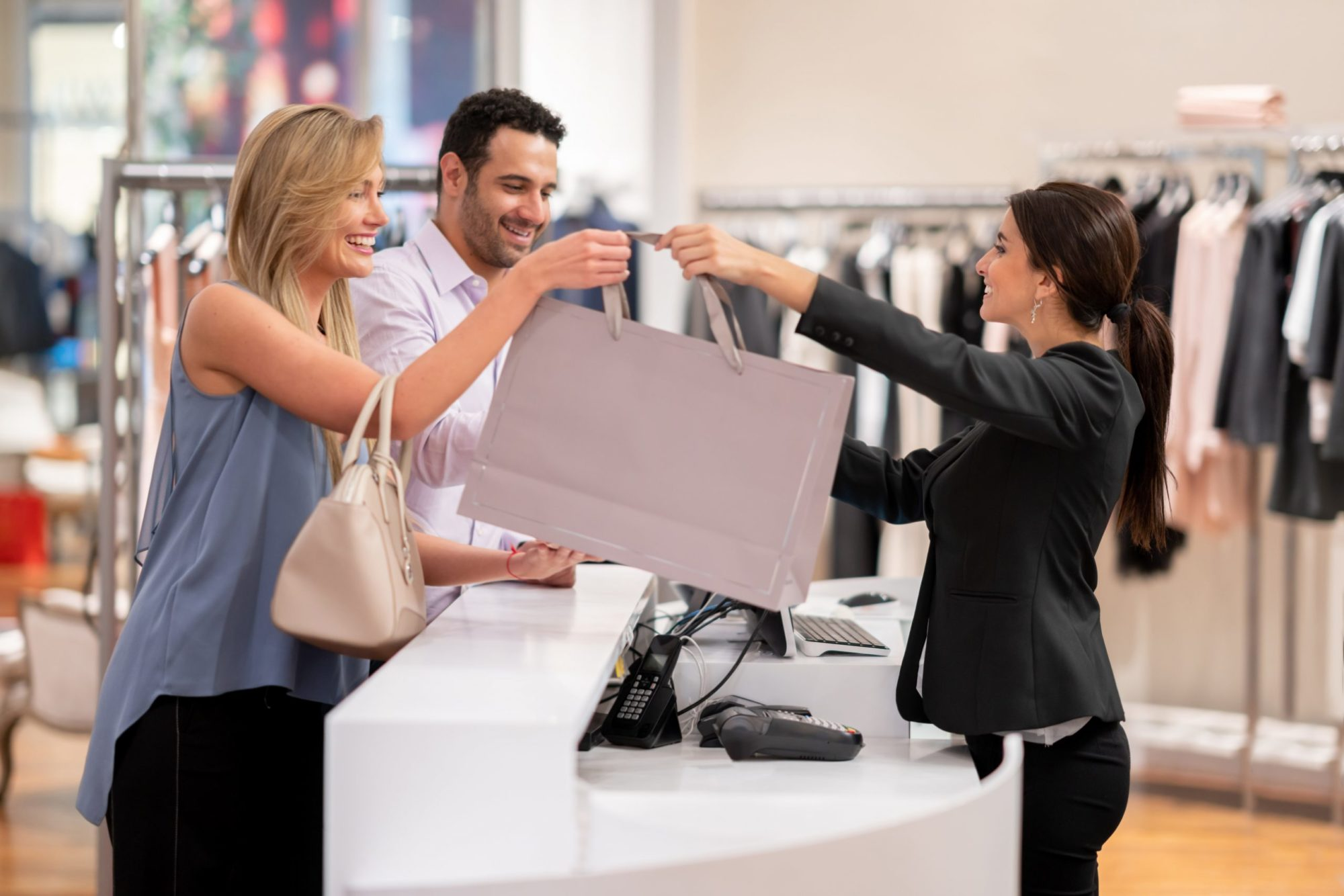 couple shopping at clothing store paying cashier