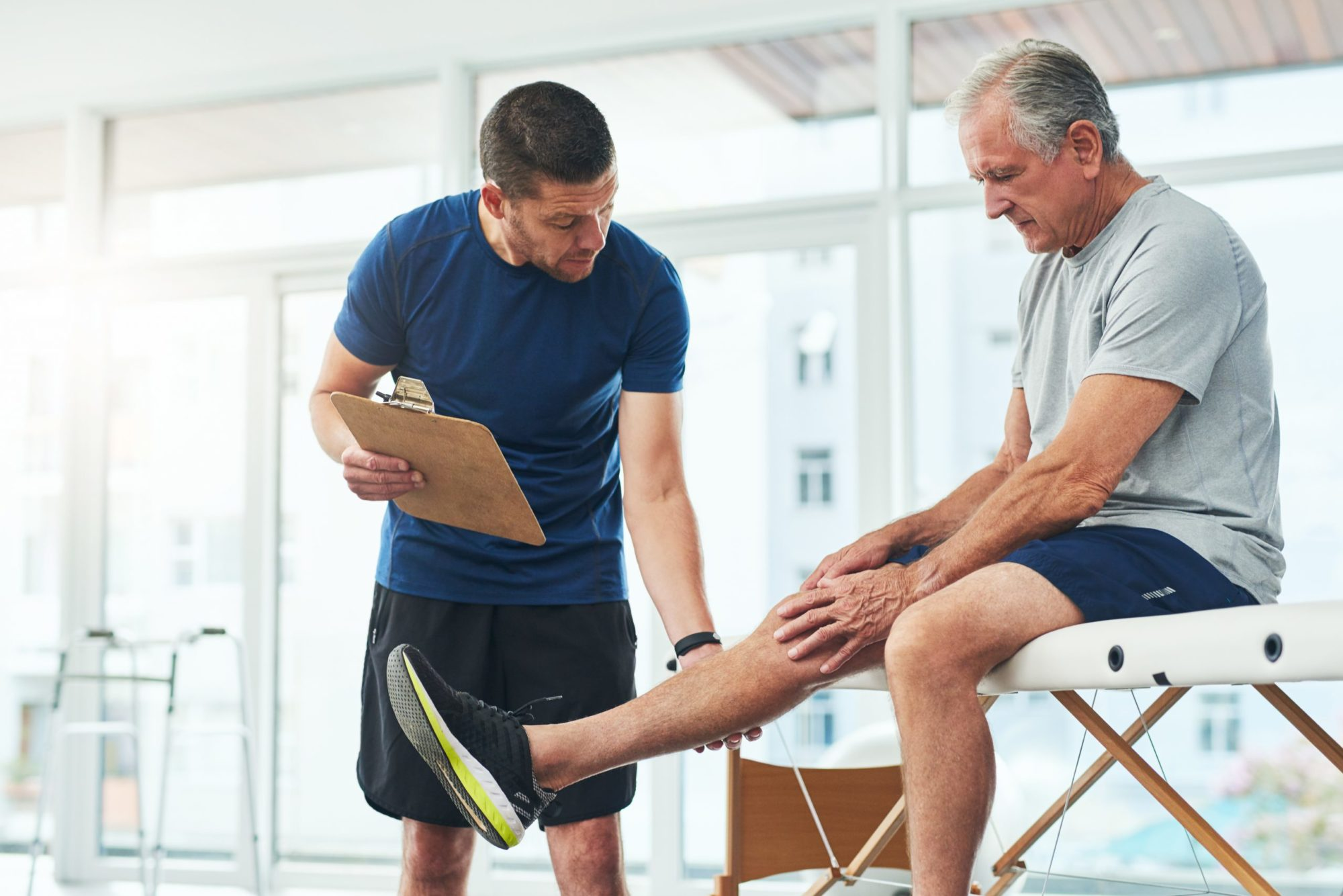 Cropped shot of a handsome young male physiotherapist doing a consultation and assessment with a senior patient
