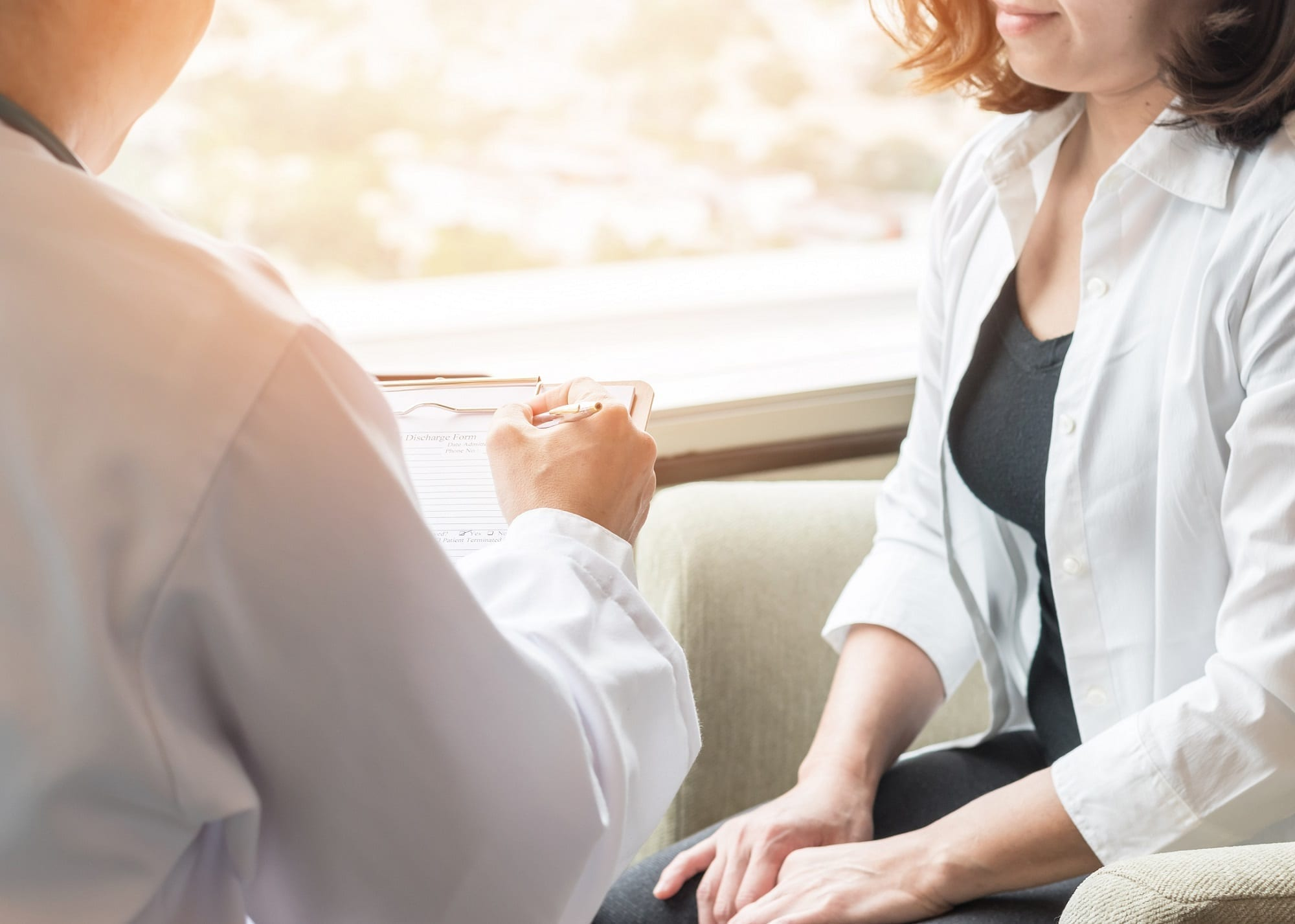 Female Doctor Consulting Female Patient Stock Photo