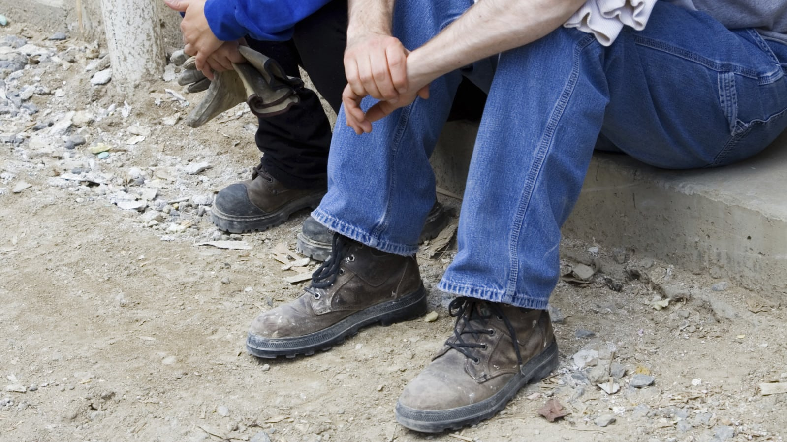 Construction Worker Sitting On A Sidewalk Stock Photo