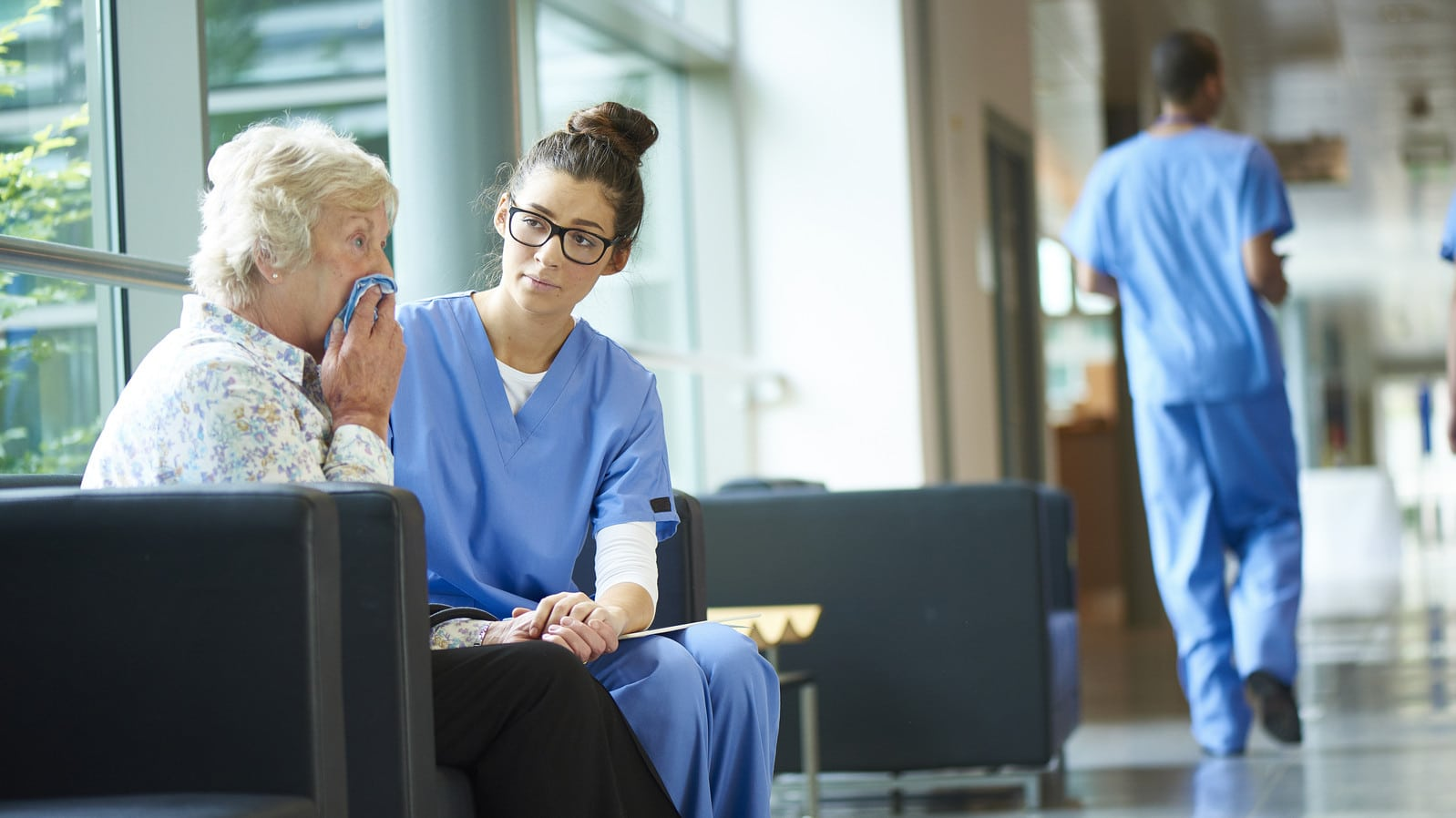 Nurse Consoling Elderly Woman Stock Photo