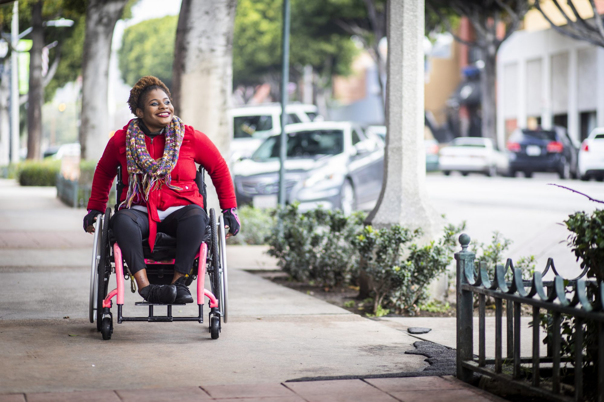 A woman rolling her wheelchair down the sidewalk in Boston