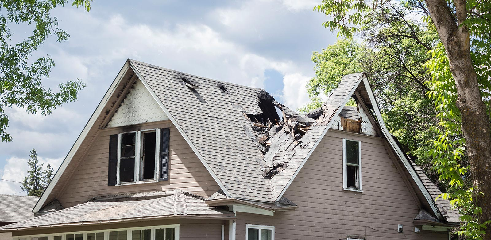 A Boston home with significant roof damage after a fire