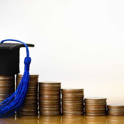 A graduation cap propped on stacks of coins.